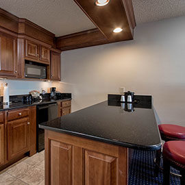 In-room bar with stools and kitchen